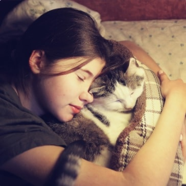 A girl and her cat sleeping together in bed