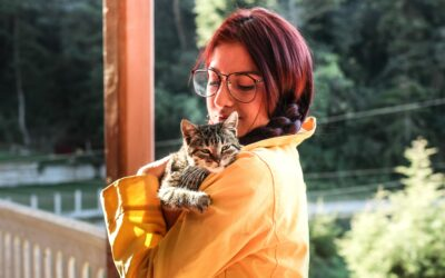 woman-in-yellow-raincoat-holding-cat-wont-leave-me-alone